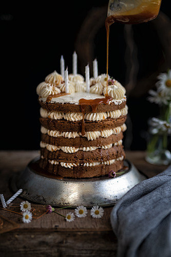 Earl Grey layer cake with Swiss buttercream with caramel being poured on