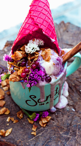 Fruits of the forest ice cream served in a cup with a pink cone and coconut flakes