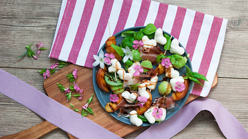 Summer salad with grilled peaches, ham, mozzarella hearts and basil