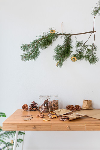 Pine branch decorated with apple rings above biscuits and pine cones on table