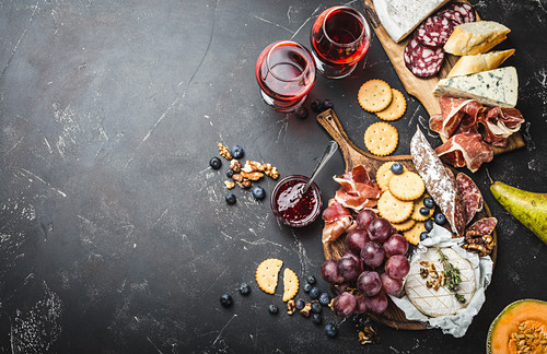 A platter of cheese, meat, crackers, bread, grapes and nuts with red wine