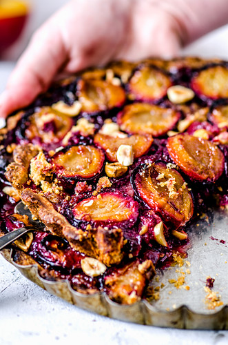 Cut pie with plums and hazelnuts