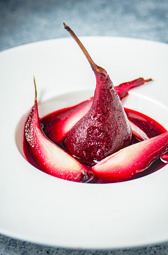 Red wine infused pears on a white plate