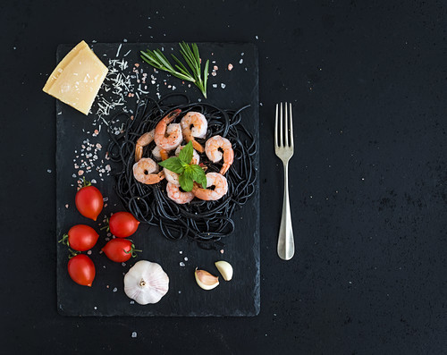 Black pasta spaghetti with shrimps, basil, pesto sauce, garlic, parmesan cheese and cherry-tomatoes on a slate tray over black grunge backdrop