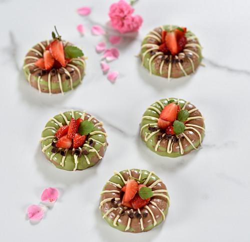 Vegan matcha and chocolate cakes with white chocolate glaze and fresh strawberries