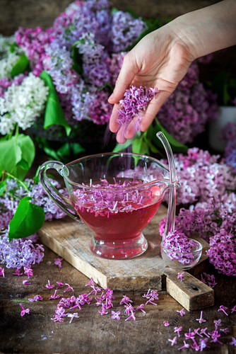 Lilac flowers being sprinkled into homemade lilac syrup