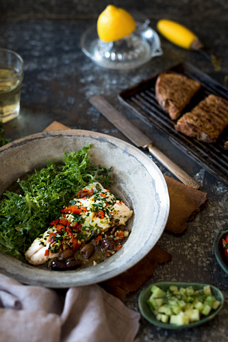 Pan fried hake with tomatoes, olives and garlic served with griddled sourdough and salad