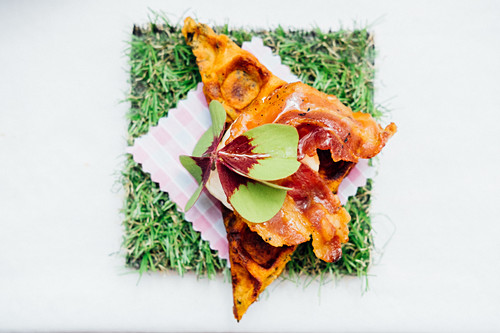 Waffle with crispy bacon, maple syrup and a garnish of oxalis leaf (a type of sorrel)