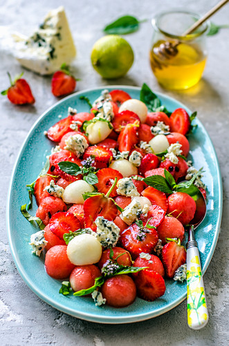 Salad from watermelon, melon, strawberry, basil and blue cheese with honey