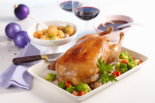 Roast duck with a minced meat stuffed, vegetables and potato and almond bites