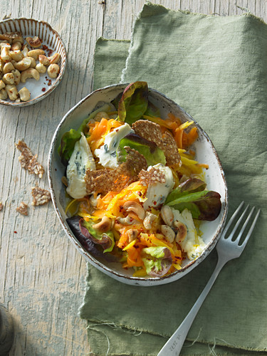 Raw pumpkin salad with cashew nuts, yellow carrots and coriander with blue cheese