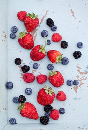 Strawberries, raspberries, blueberries and blackberries on a mint coloured tray