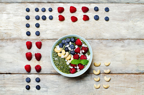 Spinach smoothies breakfast bowl with coconut flakes, raspberry, blueberry and cashews