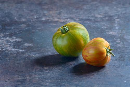 Green and orange zebra tomatoes on a metal sheet