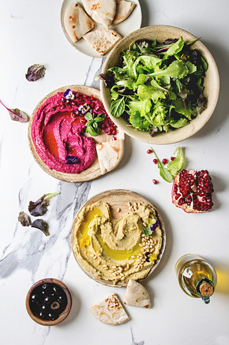 Variety of homemade traditional and beetroot spread hummus with pine nuts, olive oil, pomegranate served on ceramic plates with pita bread and green salad