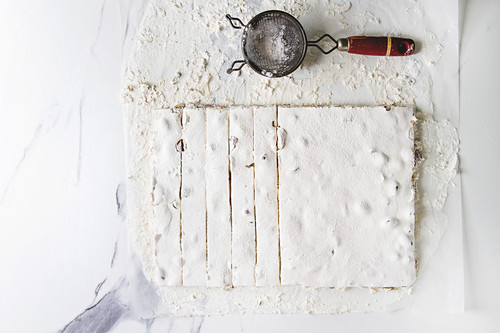 Homemade honey nuts nougat turron sliced on crumpled paper with vintage sieve and sugar powder over white marble background