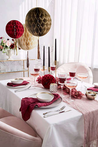 Festive table in pink and white with honeycomb balls as decoration