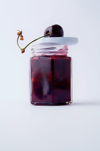 A jar of cherry jam against a white background