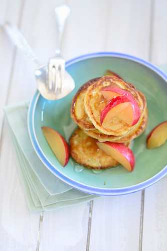 Mini pancakes served with plum slices