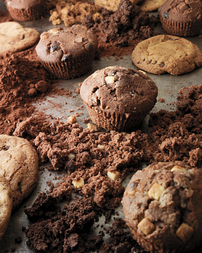 Cookies and muffins on a baking tray surronded by crumbs