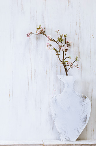 A homemade painted plywood vase, with a cherry and apple blossom branch