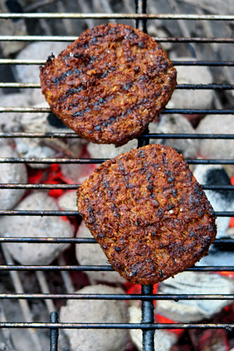 Vegan burger patties over a charcoal grill (top view)