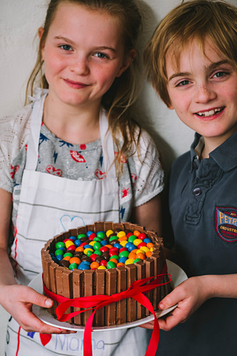 Kids made a Mother's Day cake with chocolate and candy, with a red ribbon