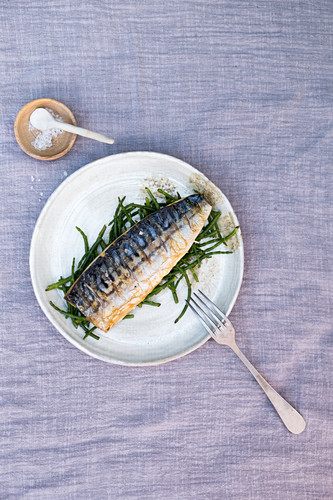 Grilled mackerel with samphire on a ceramic plate with a little bowl of salt on a linen cloth