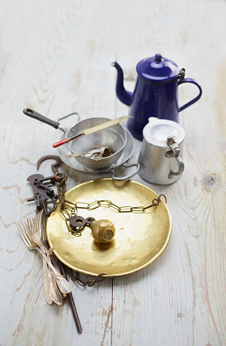 An antique brass scale, metal crockery and silver cutlery