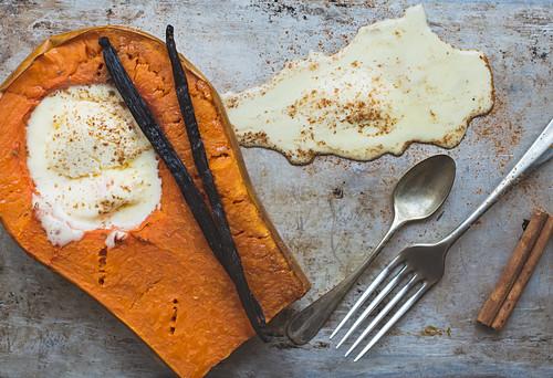 Backed pumpkin half with a scoop of vanilla ice-cream, vanilla sticks, cinnamon, a fork and a tea-spoon
