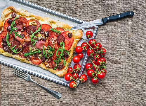 Homemade square pizza with meat, salami, cherry-tomatoes and fresh arugula on a silver tray