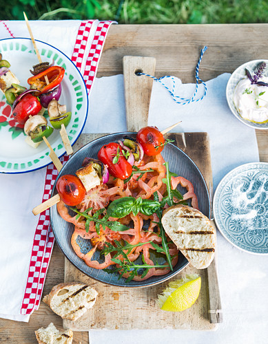 Tomato salad with rocket and grilled vegetable skewers with peppers, red onions, feta cheese and cherry tomatoes