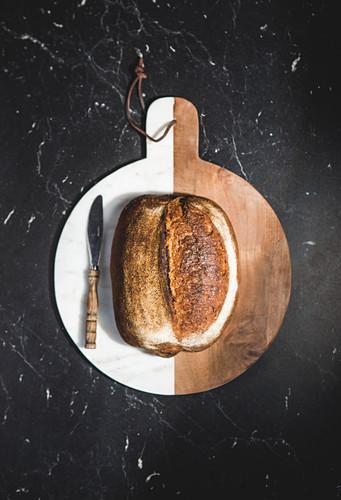 Kleiner Brotlaib mit Messer auf weiss-braunem Holzschneidebrett (Aufsicht)