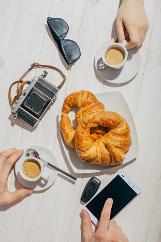 Hands holding espresso coffee cups and croissants with sun light and retro camera and sunglasses on a table