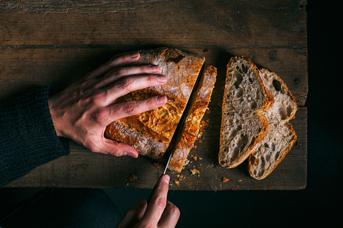 Hand cutting a slice of bread on wooden table