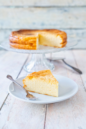 Classic cheesecake on a cake stand and a slice on a plate