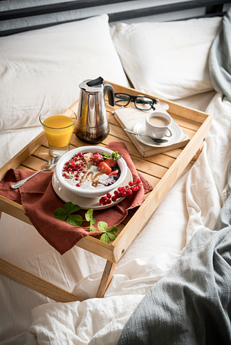 A breakfast tray with chia pudding, coffee and orange juice on a bed