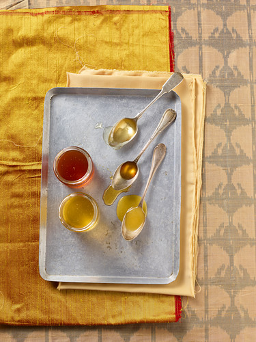 Various types of honey in glass jars and on spoons