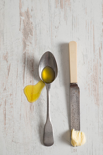 Olivenöl auf Löffel und Butter auf Messer