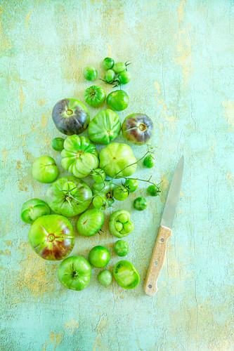 Grüne Tomaten und Messer auf altem Tisch