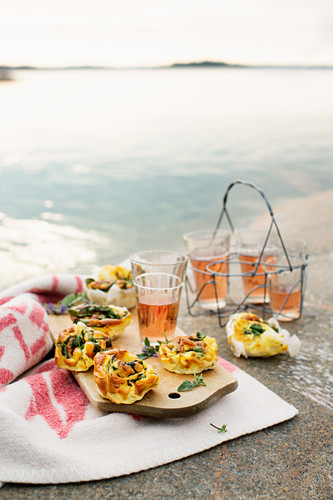 Mini omelettes with spinach and taleggio and drinks for a picnic by a lake