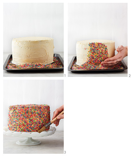 A birthday cake being decorated with sugar sprinkles