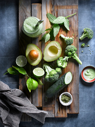 Flat lay of arranged greens of fresh broccoli with cucumber and avocado among green herbs on wooden board