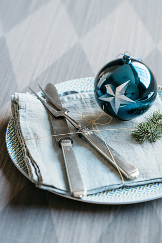 A Christmas place setting decorated with a blue bauble