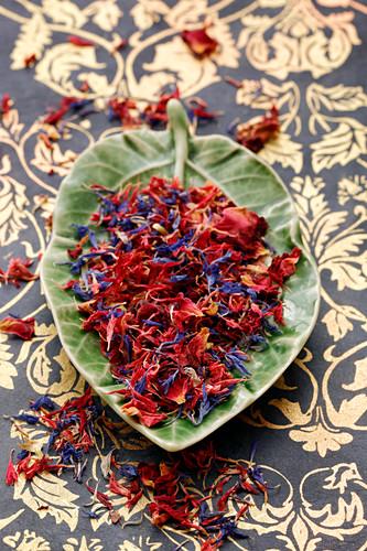 Getrocknete Blütenblätter von Kornblume und Rose in Schale