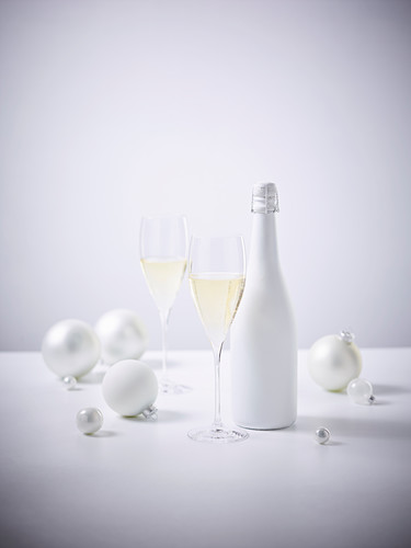 Sparkling wine in glasses between white Christmas baubles and a white wine bottle