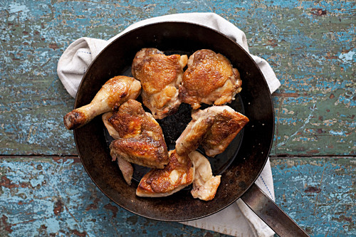 Golden chicken thighs and wings in a pan