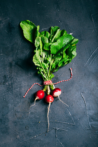 Radish with leaves on a dark background