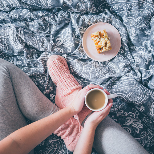 A woman wearing bed socks, sitting an a bed wth cup of coffee and piece of cake