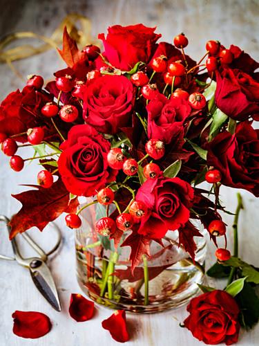 Weihnachtsstrauß aus roten Rosen und roten Beerenzweigen